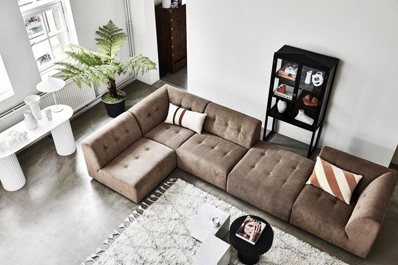 elegancka narożna brązowa sofa Vint od HK Living wjasnym salonie zciemną podłogą przy jasnym dywanie