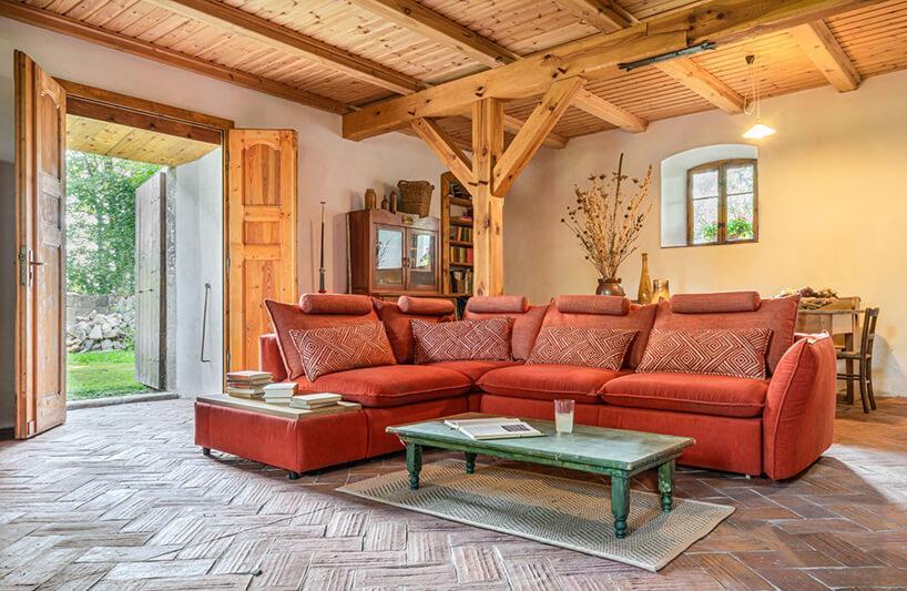 ceglana narożna sofa modułowa Gala Collezione wsalonie zdrewniany filarami