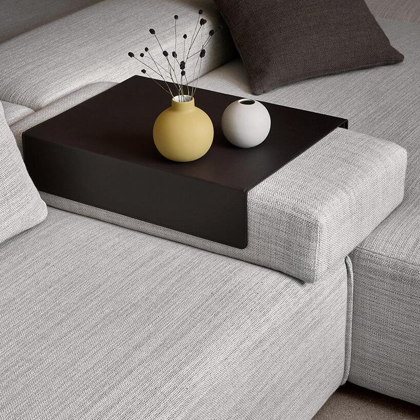 szara kanapa zszerokim podłokietnikiem zczarnym elementem zżółtą oraz białą kulką