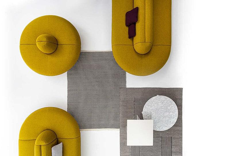 musztardowe kanapy przy szarym prostokątnym elemencie na środku