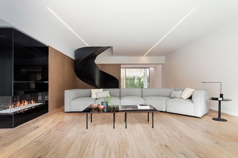 zakręcone czarne matowe schody na piętro nad szarą dużą kanapą