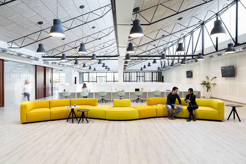 industrialne wnętrze zmocno kontrastującą żółtą długą kanapą