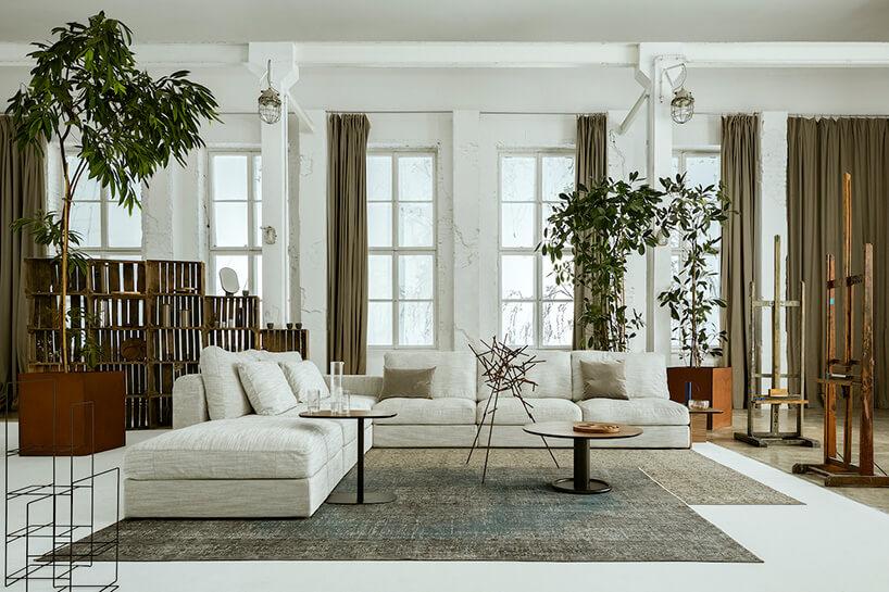 salon zdużym udziałem kanapa wkolorze białym oraz drewnianych dodatków izieleni
