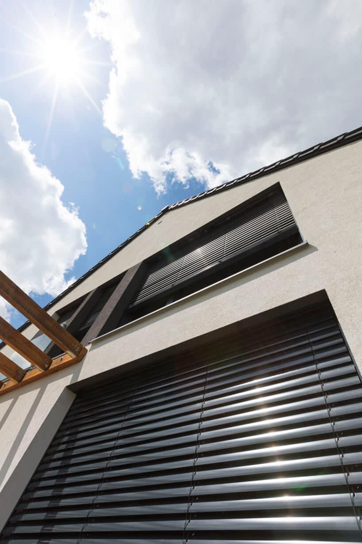 nowoczesne żaluzje zewnętrzne wkolorze szarym przy białej fasadzie