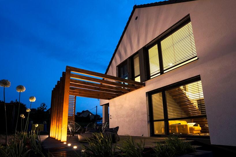 dom zdrewnianą konstrukcją na tarasie nocą