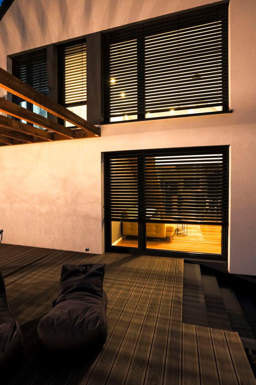 dwie czarne żaluzje zoświetlonymi oknami domu
