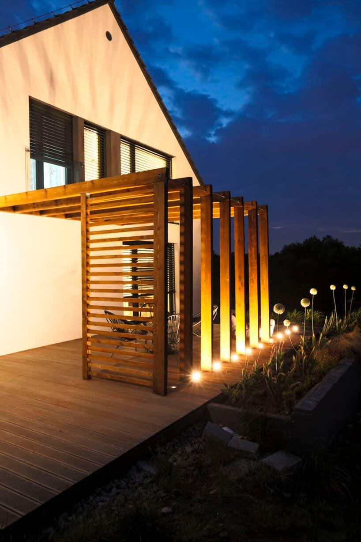 drewniana kwadratowa konstrukcja tarasowa przy białym domu