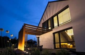dom z drewnianą konstrukcją na tarasie nocą