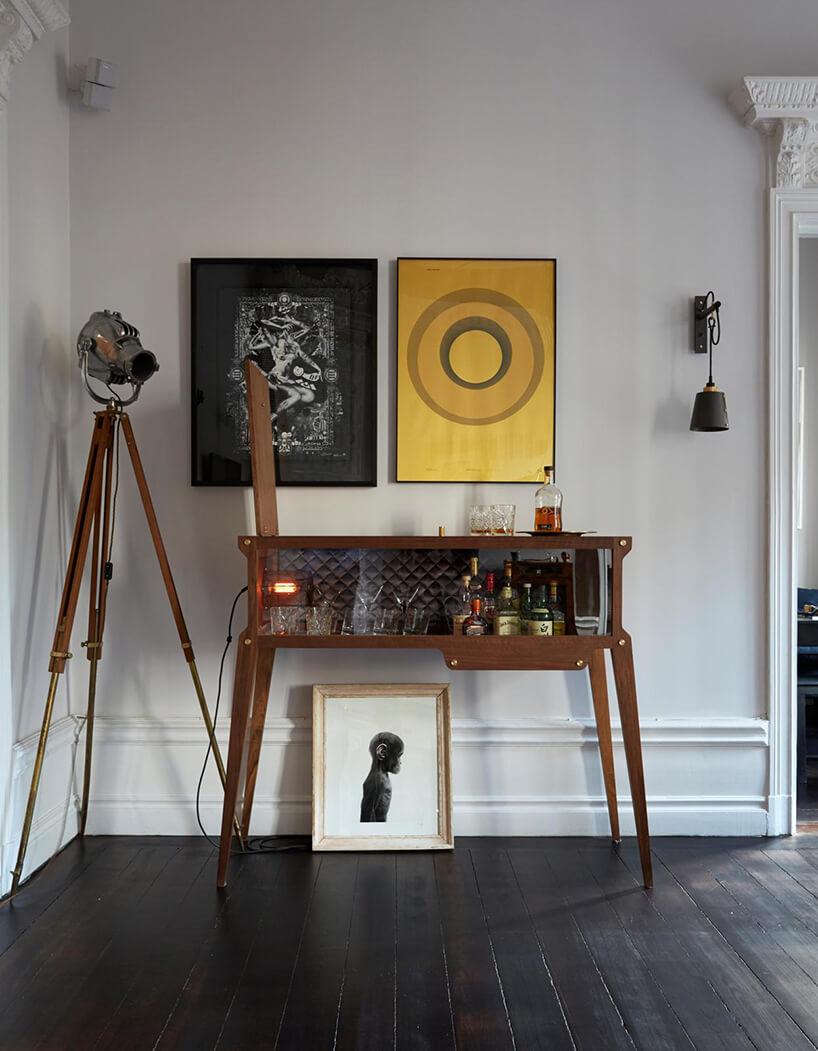 elegancki drewniany barek na wysokich nogach obok starej lampy studyjnej na trzech drewnianych nogach