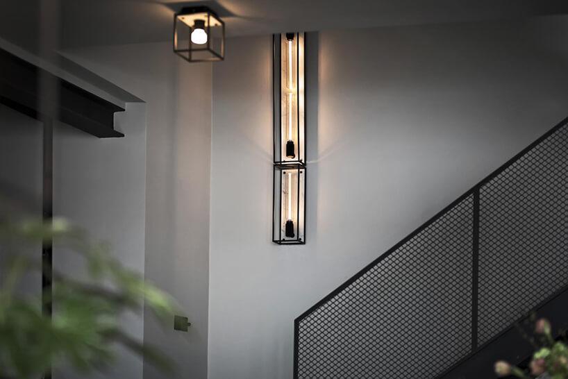 wyjątkowe dwie podłużne lampy naścienne jako tło dla punktowej lampy sufitowej wczarnej sześciennej ramie