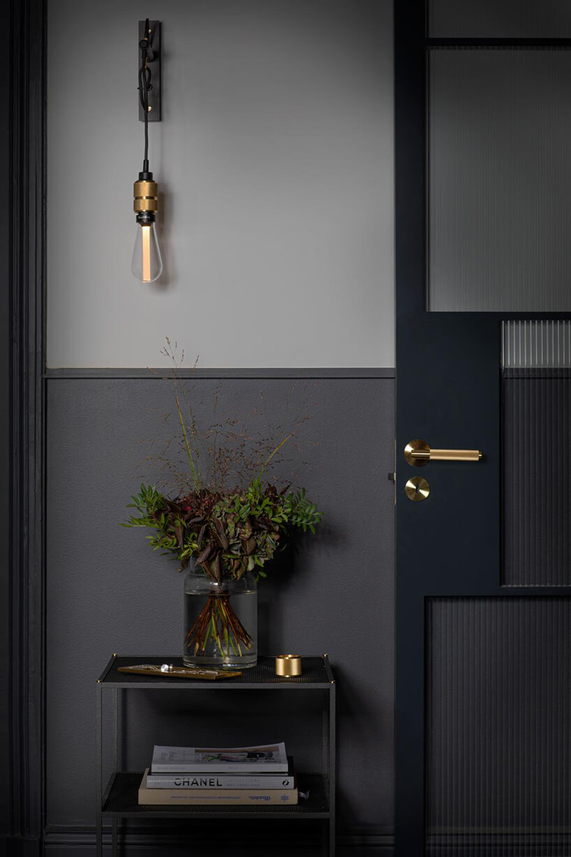 wyjątkowa lampa ścienna ze złotym elementem na kablu na tle szarej ściany