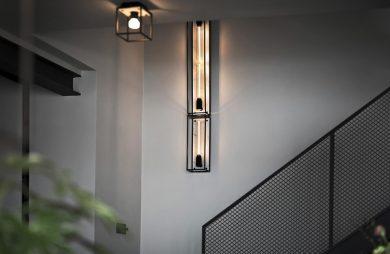 wyjątkowe dwie podłużne lampy naścienne jako tło dla punktowej lampy sufitowej w czarnej sześciennej ramie
