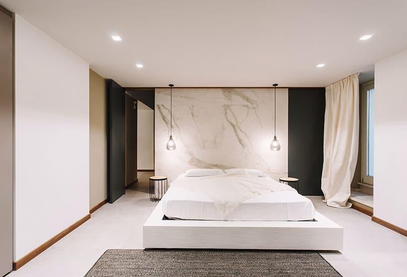 duży biały kamień na ścianie za dużym łóżkiem weleganckiej sypialni