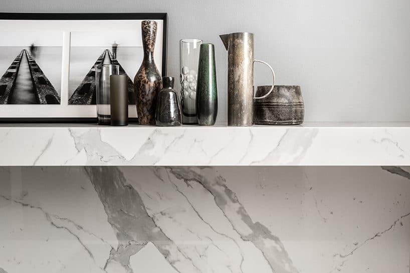 elegancki biały kamień na ścianie ijako półka pod różnymi wazonami
