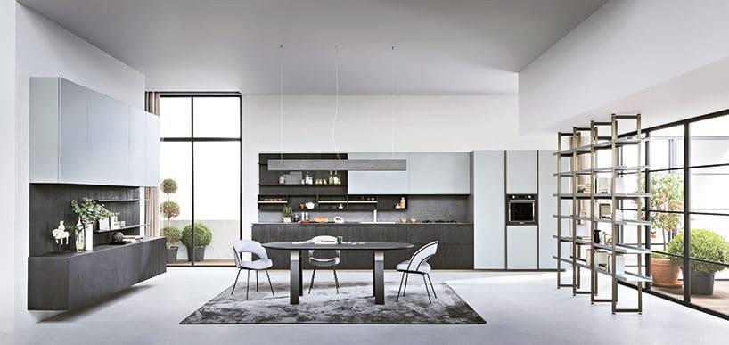 elegancka biała kuchnia zciemną szarą dolną zabudową idużym czarnym stołem pośrodku