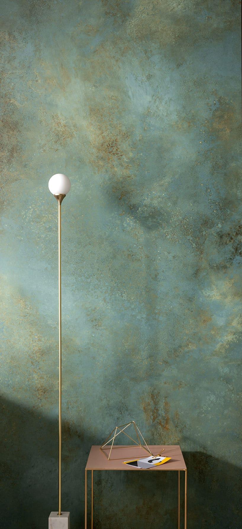 zielony kamień zbrązowymi drobinkami na ścianie jako tło dla małego stolika ipodłogowej lampki