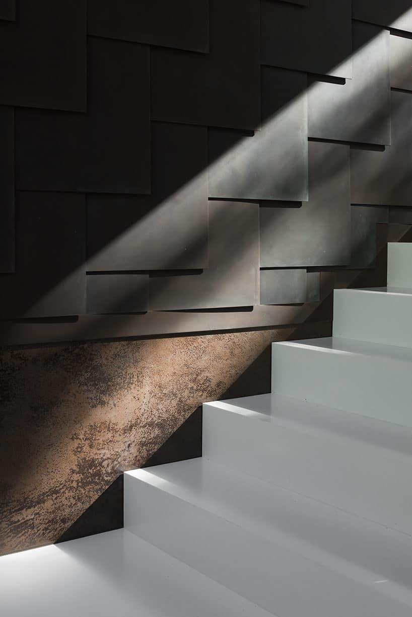 eleganckie białe schody na tle ściany zkamiennych płyt