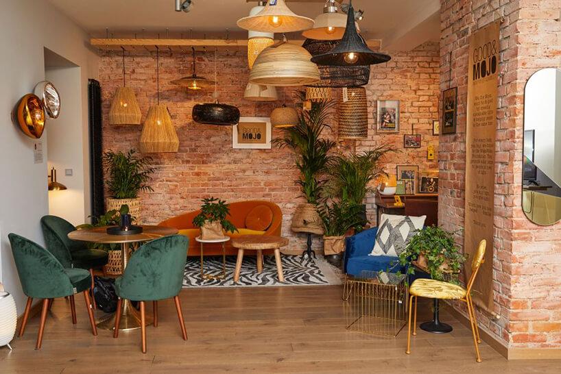 aranżacja wnętrza zzielonymi fotelami przy okrągłym stoliku na tle ceglanej ściany pod wieloma różnymi lampami