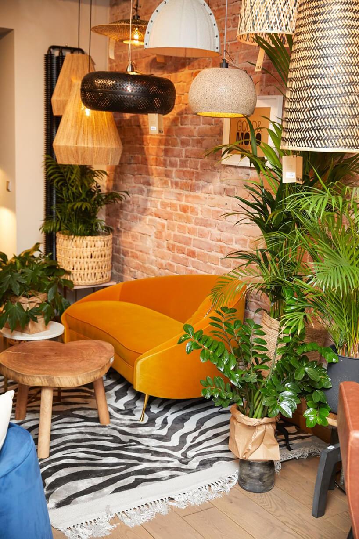 małą pomarańczowa sofa przy małym stoliku zblatem wkształcie drzewa na tle ceglanej ściany