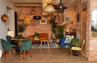 aranżacja wnętrza z zielonymi fotelami przy okrągłym stoliku na tle ceglanej ściany pod wieloma różnymi lampami