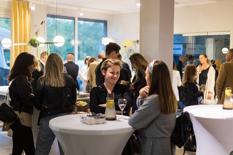 goście przy białych wysokich stolikach podczas spotkania Design od kuchni wSopocie