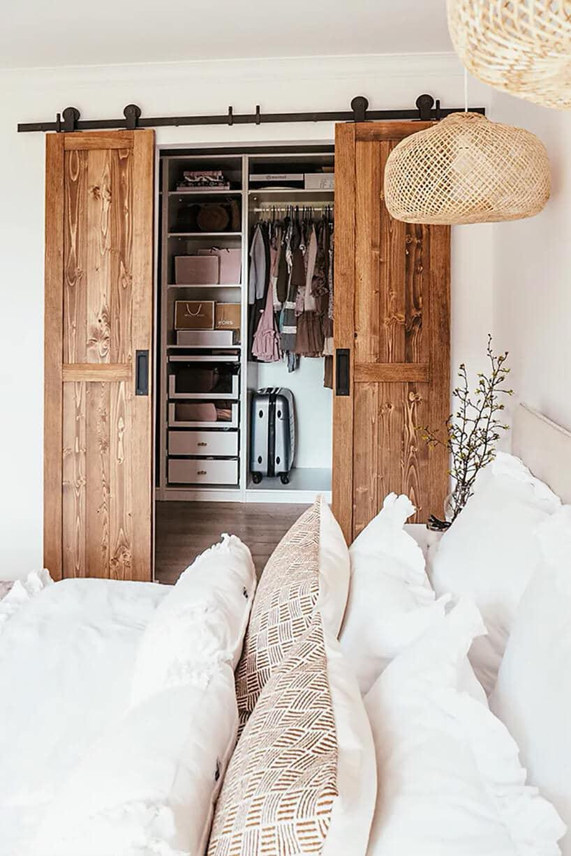 sypialnia zdużymi łóżkiem ibiałymi poduszkami oraz przesuwnymi dębowymi drzwiami na szynie
