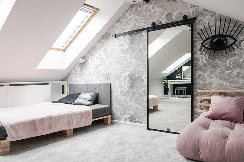 jasno pudrowo różowe łóżka wpokoju na poddaszu zprzesuwnymi drzwiami zlustrem