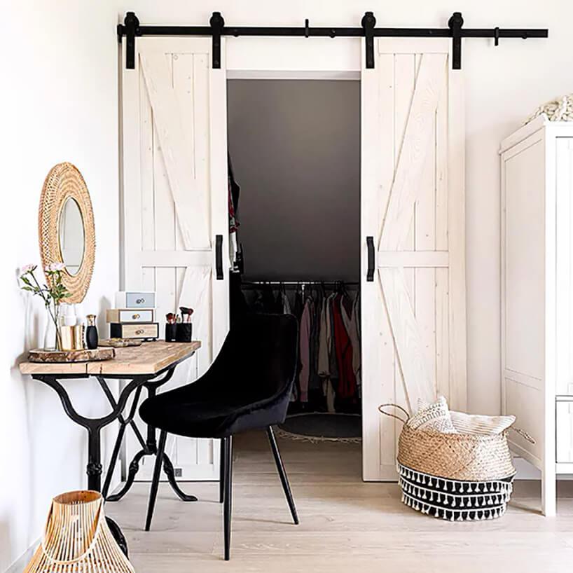 czarne krzesło obok miejsca do makijażu zdrewnianym stolikiem