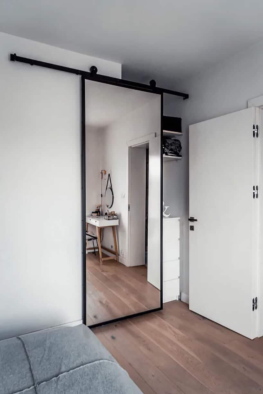 lustrzane przesuwne drzwi na czarnej szynie iczarnym obramowaniu