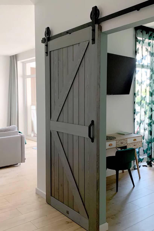 zielone drzwi wstarym stylu jak od stodoły na szynie