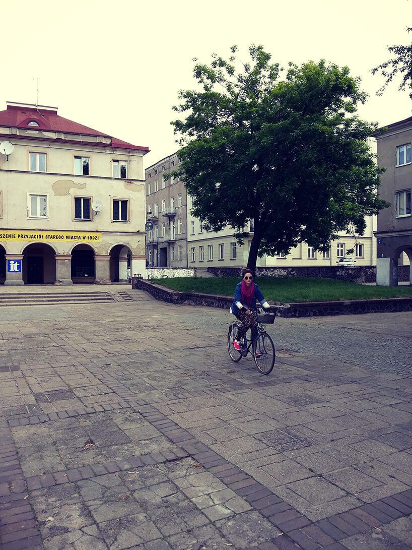 kobieta jadąca na rowerze po dużym placu
