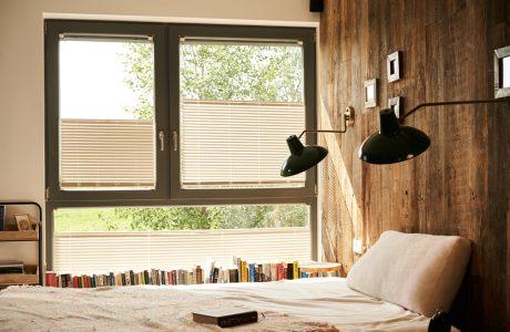 sypialnia ze ściana wyłożoną starym drewnem na tle okna z beżowymi dwukierunkowymi osłonami okiennymi od ANWIS