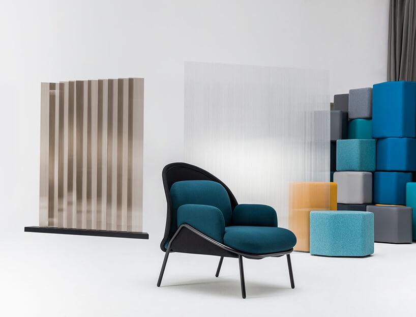 nowoczesne krzesło zczarnym stelażem iniebieskim siedziskiem obok kolorowej ściany zklocków