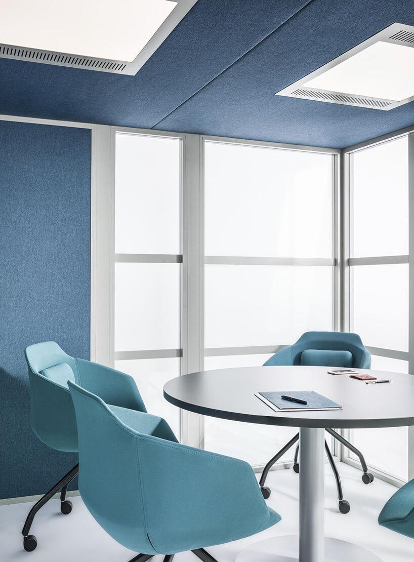 wnętrze Wnętrze Hako Meeting Room od MDD boxu wopen space zokrągłym białym stolikiem iniebieskimi fotelami na kółkach