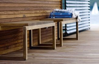 dwie drewniane ławeczki z niebieskimi ręcznikami na tle drewnianej podłogi i ściany