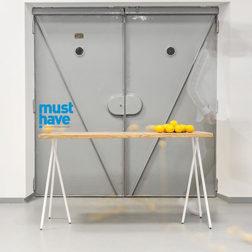 stół zsześcioma nogami na tle drzwi do windy towarowej
