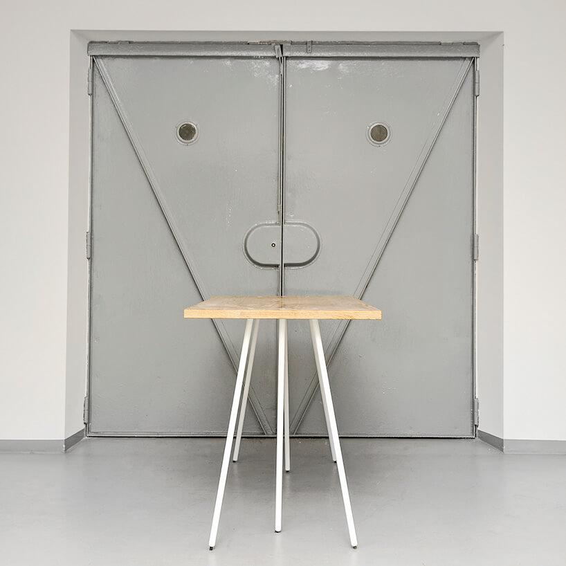 stół zsześcioma nogami widziany zboku na tle drzwi do windy