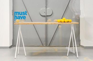 must have stół z dodatkowymi nogami z cytrynami na blacie na tle szarych drzwi do windy