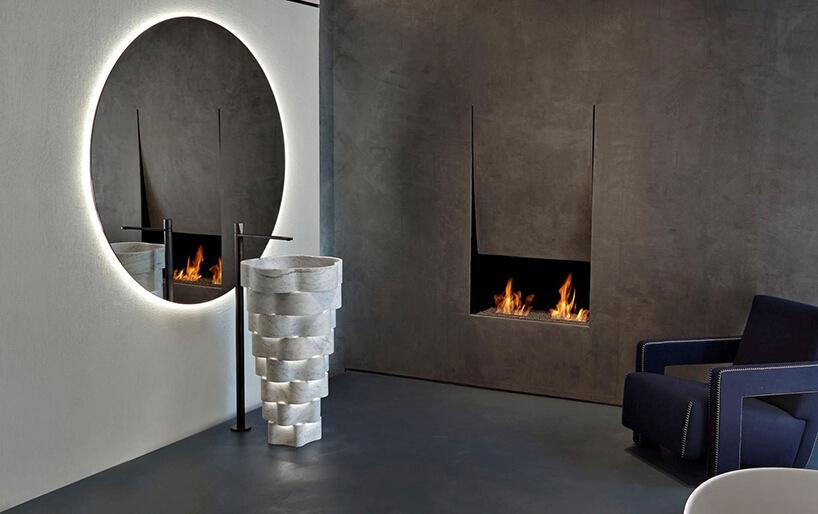 eleganckie wnętrze zkamienną ścianą iwtopiony wnią kominek