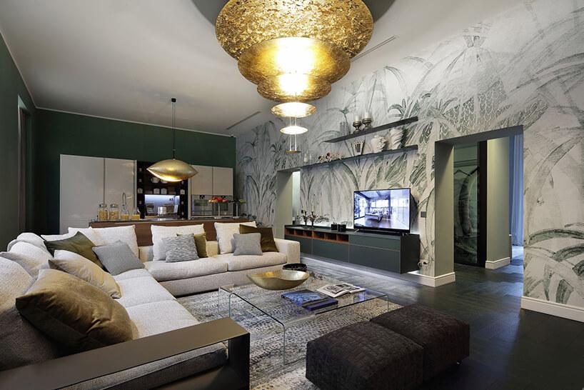 eleganckie wnętrze salonu zaneksem kuchennym zwielkim złotym żyrandolem