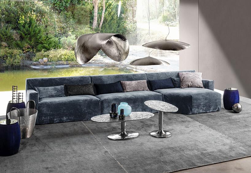 duża niebieska sofą obok dwóch małych stolików pod trzema lampami wiszącymi zmetalowymi kloszami
