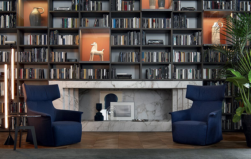 salon zdwoma eleganckimi niebieskim fotelami na tle kamiennego kominka iściany pełnej książek