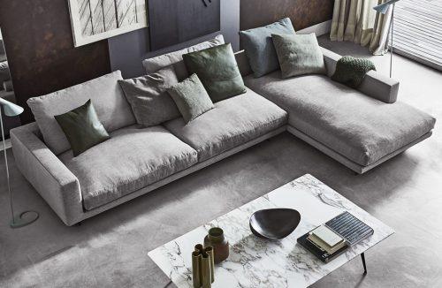 nowoczesny salon z dużą szarą sofą i niskim kamiennym stolikiem