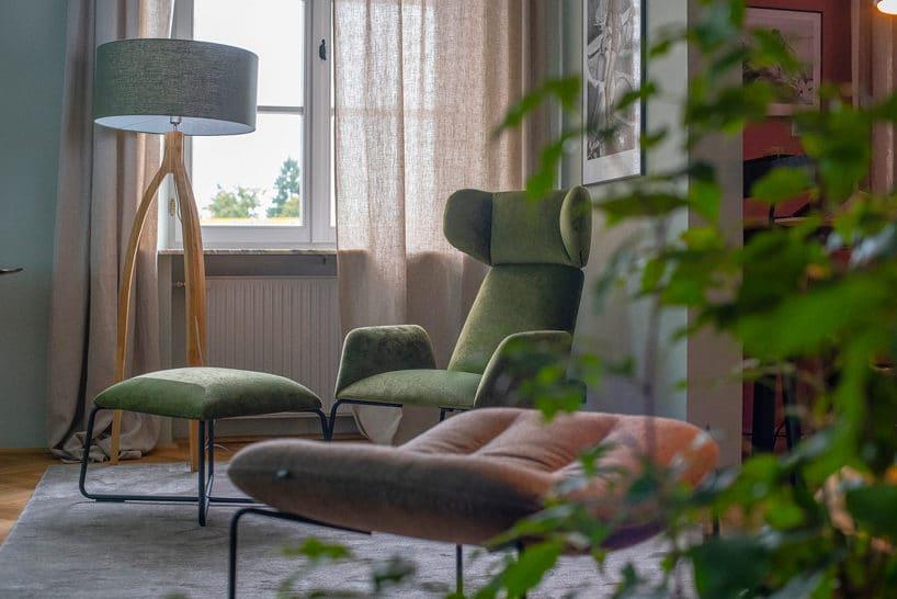 zielony fotel zwysokim oparciem izałówkiem na dtle stojącej lampy na trzech drewnianych nogach
