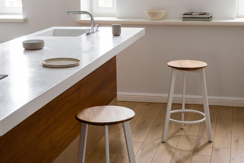 dwa wysokie stołki zdrewnianym siedziskiem na białych nogach przy biało drewnianej wyspie kuchennej