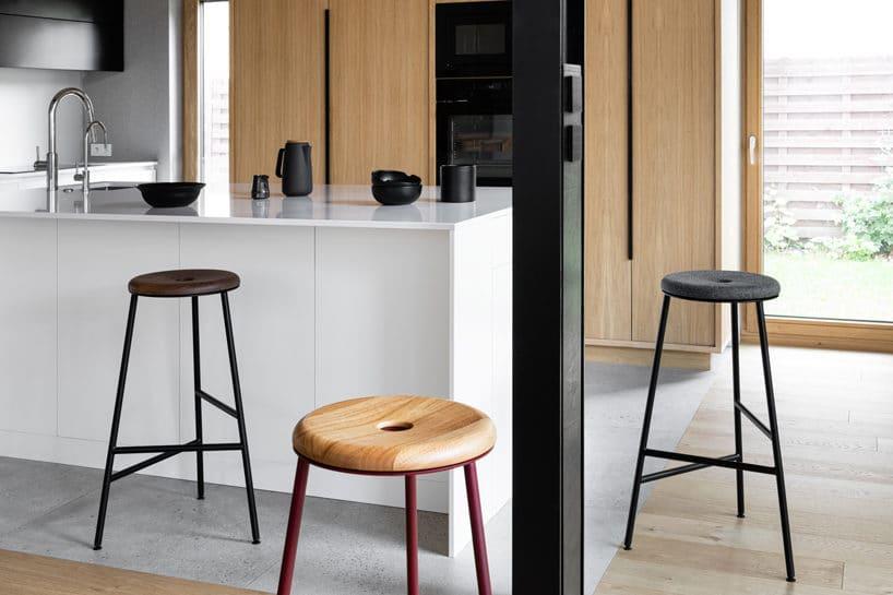 nowoczesne wysokie stołki zwklęsłym siedziskiem przy białej wysokiej wyspie kuchennej