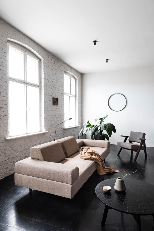 jasna sofa na czarnej podłodze wsalonie zbiałymi ścianami