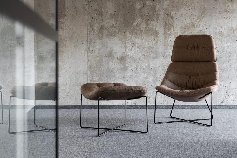 brązowy fotel zzagłębieniem na czarnym cienkim metalowym stelażu obok podnóżka na tle betonowej surowej ściany