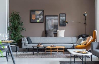 szara nowoczesna niska sofa na tle jasno brązowej ściany