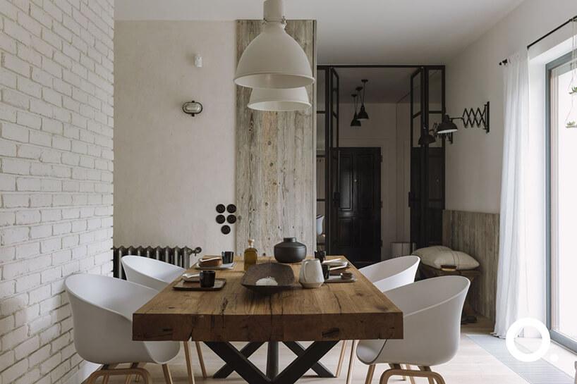 jasne wnętrze jadalni zdużym stołem zdrewnianym grubym blatem zbiałymi plastikowymi fotelami na drewnianych nogach